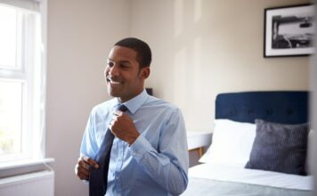 Young Man Getting Dressed In Bedroom For First Day At Work In Office