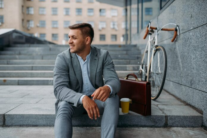 Businessman with bike having lunch at the office