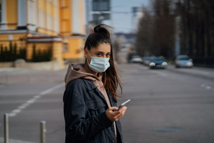 Girl in protective mask using smartphone outdoors. COVID 19. World coronavirus pandemic